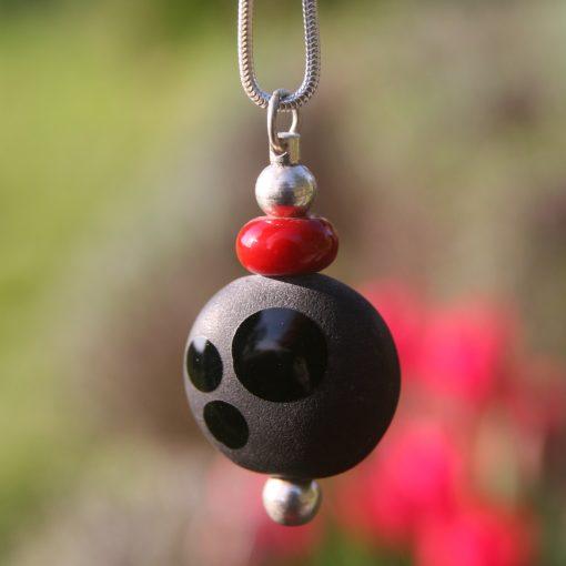 voici un joli pendentif de createur avec une perle de verre de Murano filee au chalumeau avec un jeu de noir mat sablé et noir brillant