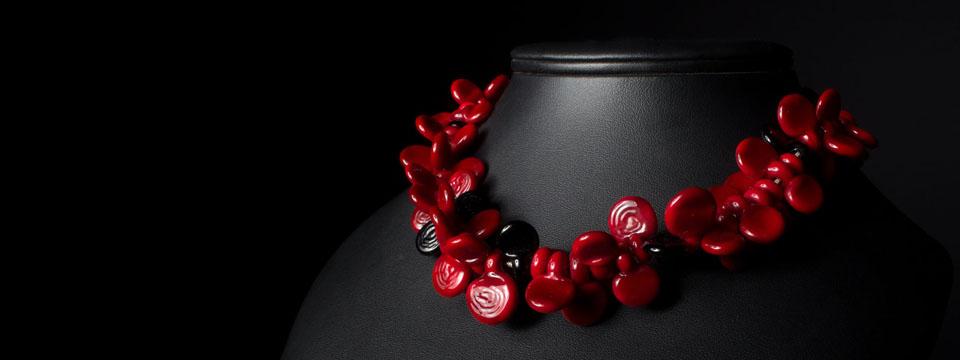 Voici un collier en perles de verre de murano de coloris rouge majoritairement avec quelques perles noires. Les perles ont toute des formes différentes pour donner du relief au collier qui se compose de 55 perles.